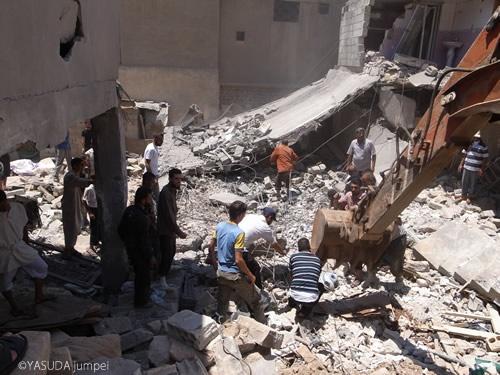 重機を使って空爆被害者を捜索する住民=2012年7月15日