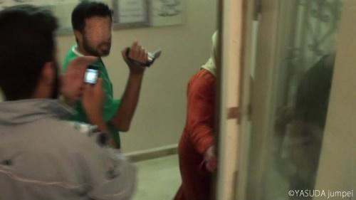 政府軍の戦車砲攻撃による負傷者を秘密病院に運ぶ様子を撮影する医師と反政府側メディアセンターの活動家=2012年7月14日