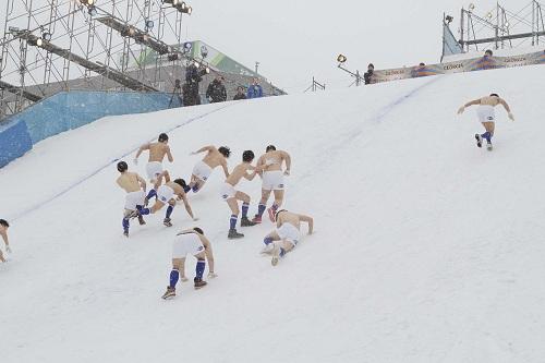 上半身裸でジャンプ台を駆け上がる男たち