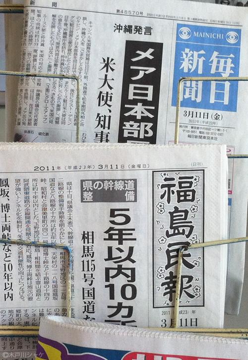 駅のスタンドに刺さったままの新聞