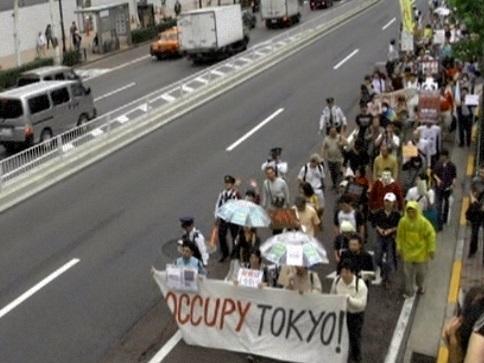 「OCCUPY TOKYO(東京を占拠せよ)」と書かれた横断幕を掲げたデモ行進