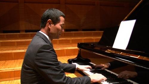 テレビCMのためにピアノを演奏する桑田真澄さん