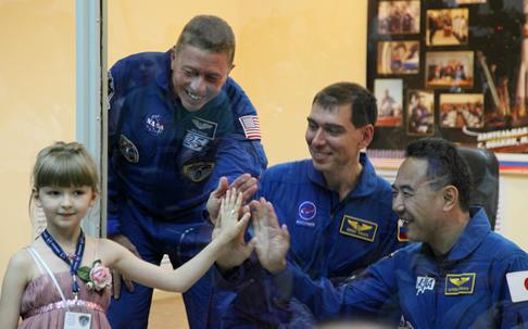 ロシア連邦宇宙局主催のバッチデザインコンテスト優勝者の少女と共に写真を。