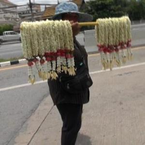 タイで渋滞中の車の間を練り歩き花を売る女性の正体は? 実は……