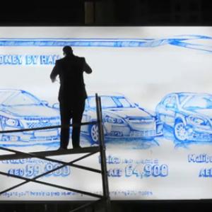 青マジックだけで看板に車のイラストを描く人 朝も昼も夜も描き続ける